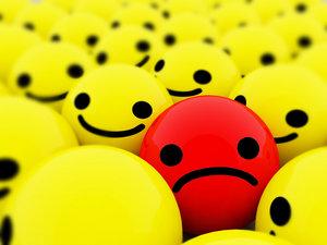 cara triste entre caras felizes